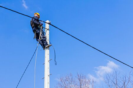 Photo pour Technician works high up on a power pole - image libre de droit