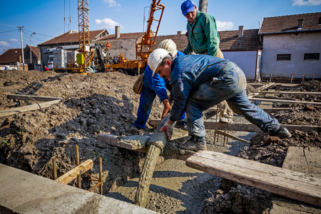 Foto de Construction workers are pouring concrete in building foundation, directing the pump tube on right direction. - Imagen libre de derechos
