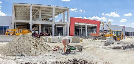 Foto de Panoramic view on landscape transform into urban area with machinery, people are working on construction site. - Imagen libre de derechos