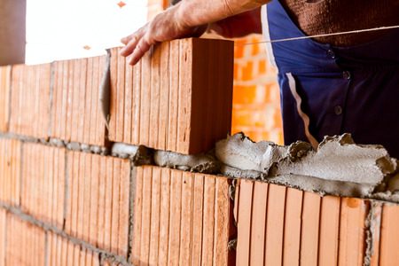 Foto de Mason, bricklayer worker is using red blocks to mount a wall next the string line to be straight. - Imagen libre de derechos