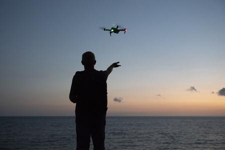 Foto de A man runs a quadcopter over the ocean. Selective focus. - Imagen libre de derechos