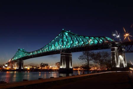 Foto de Jacques Cartier Bridge Illumination in Montreal, reflection in water. Montreal's 375th anniversary. Luminous colorful interactive Jacques Cartier Bridge. Bridge panoramic colorful silhouette by night. - Imagen libre de derechos