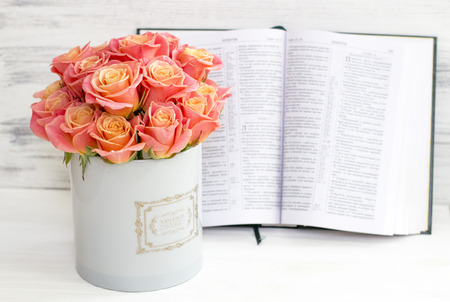 Photo for Roses in a round box and the Bible. Beautiful pink roses on a white wooden background. Beautiful pink roses and the Bible. Roses in a Hat Box - Royalty Free Image