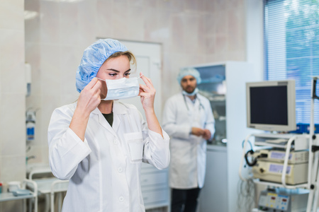 Foto de Confident female doctor putting on medical face mask while preparing for operation, her male colleague standing behind her - Imagen libre de derechos