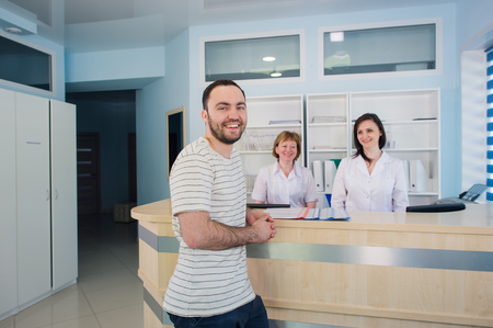 Photo for Male patient with doctor and nurse at reception desk in hospital - Royalty Free Image