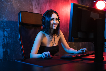 Photo pour A cute female gamer girl sits in a cozy room behind a computer and plays games. Woman live streaming computer video games to her fans. Streamer and gamer concept - image libre de droit