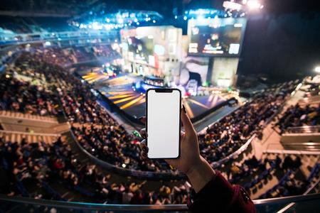 Photo pour Woman's hands using digital application on the mobile smart phone at esport event at big arena - image libre de droit