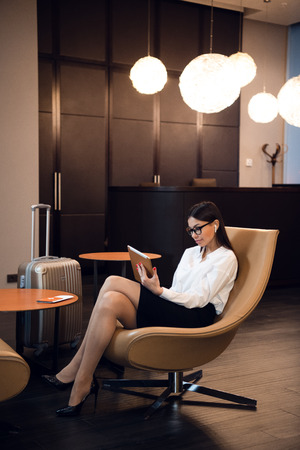 Photo for Confident businesswoman listening music on her tablet computer while sitting in chair in airport business lounge - Royalty Free Image