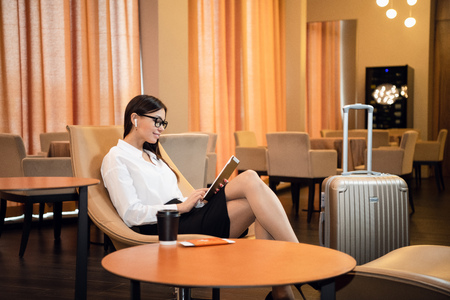 Photo pour Confident businesswoman listening music on her tablet computer while sitting in chair in airport business lounge - image libre de droit