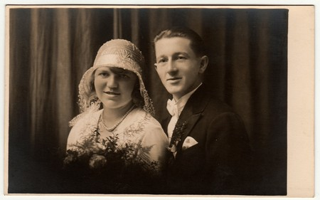 Photo for LIBEREC (REICHENBERG), THE CZECHOSLOVAK  REPUBLIC - CIRCA 1920s: Vintage photo of newlyweds. Bride wears white hat with lace (bobbin). Groom wears posh clothing, white bow-tie.  Black & white antique studio portrait. - Royalty Free Image