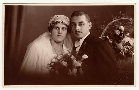 Photo for CHRASTAVA (KRATZAU), THE CZECHOSLOVAK  REPUBLIC - CIRCA 1930s: Vintage photo of newlyweds. Bride wears a veil and holds wedding bouquet. Black & white antique studio portrait. - Royalty Free Image