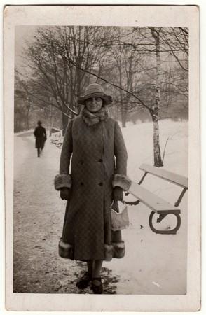 Photo pour THE CZECHOSLOVAK REPUBLIC - CIRCA 1940s: Vintage photo shows woman in a winter time. Woman wears a long coat with fur bordering.  Retro black & white photography. - image libre de droit