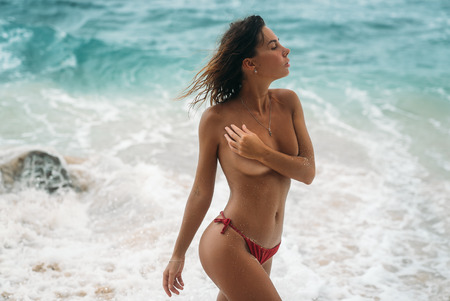 Photo for Portrait of sexy young girl in red swimsuit without bra posing on the beach. Beautiful brunette woman with long hair relaxing at the ocean. Concept of sporty model, swimwear, travel - Royalty Free Image