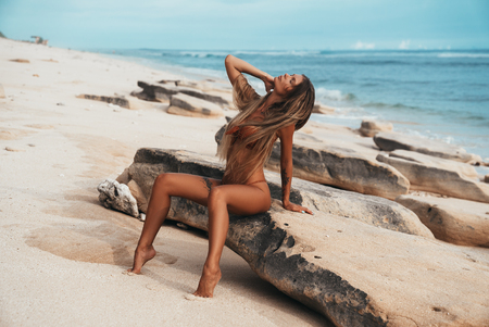 Photo for Sexy tattooed young girl in red swimsuit posing on the beach. Beautiful blonde woman with long hair relaxing at the ocean. Concept of sporty model, swimwear - Royalty Free Image