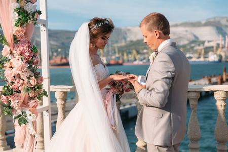 Photo pour couple in wedding arch exchange rings with lake on background, the bride with long beautiful hairs and groom in black suit look at each other in wedding day. Concept of love and family - image libre de droit