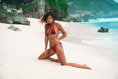 Photo for Girl Brunette with curly hair in a red bikini on the beach with white sand near the ocean on vacation. A beautiful model with a sexy body is sunbathing. - Royalty Free Image