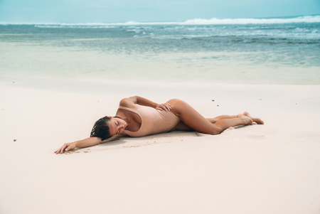 Photo for gorgeous young girl in a beige bikini lies on the beach, sunbathing near the ocean. A model with a sexy body and a sports figure in the clear sea water on the island. The concept of the weekend on vacation overseas. - Royalty Free Image