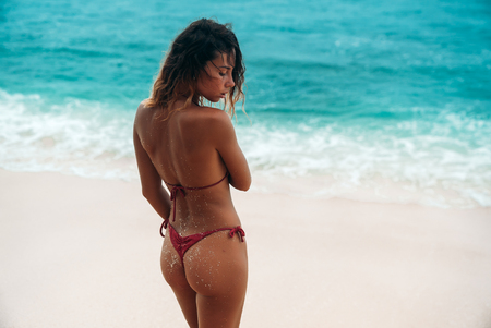 Photo for Back view, portrait of a gorgeous woman in a red bikini on the beach with white sand. Beautiful girl with a sexy tanned body on a summer vacation near the ocean. Model blonde with curly hair is posing. - Royalty Free Image