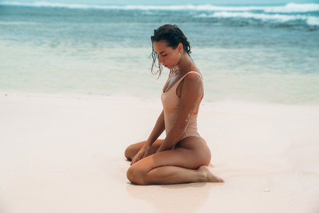 Photo for Slender girl sits on white sand against the blue ocean. A model in a swimsuit with short dark hair is sitting in a swimsuit on a white beach. - Royalty Free Image