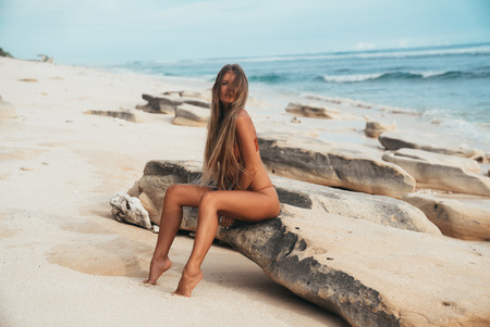 Photo for Sexy terrible long-haired girl sitting on the seashore on a rocky rock and posing. The wind plays with hair of the model, and she enjoys a summer day, her tanned body, the beach. - Royalty Free Image