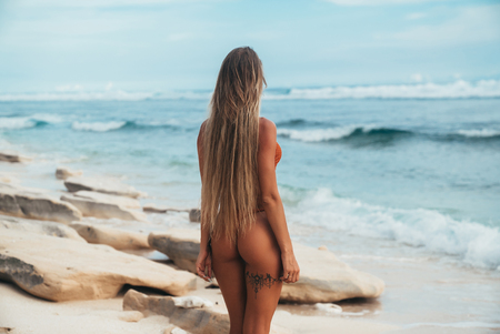 Foto de View from the back of the model with a tanned smooth skin stands on the seashore in a bikini and admires the waves coming to her feet. The concept of summer mood, rest, relaxation, travel. - Imagen libre de derechos