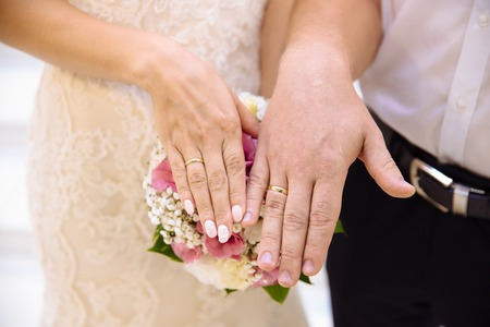 Photo for Close-up of the hands of the newlyweds with wedding rings, gently touch the wedding bouquet of peonies. - Royalty Free Image
