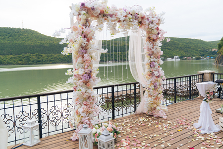 Foto de Wedding day, ceremony place for the bride and groom, decor, flowers. Concept of decor, wedding arch is decorated with flowers - pink and white peonies. - Imagen libre de derechos
