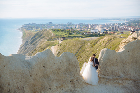 Foto de Beautiful couple of newlywed hugging at wedding day on cliff with ocean view - Imagen libre de derechos