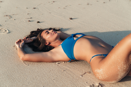 Photo for Sexy tanned girl in blue swimwear lies and sunbathes on deserted beach - Royalty Free Image