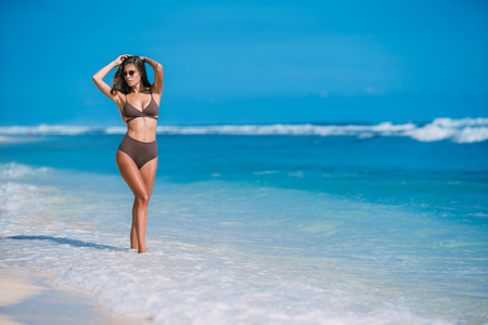 Photo for Beautiful tanned girl posing on beach with white sand and blue ocean. - Royalty Free Image