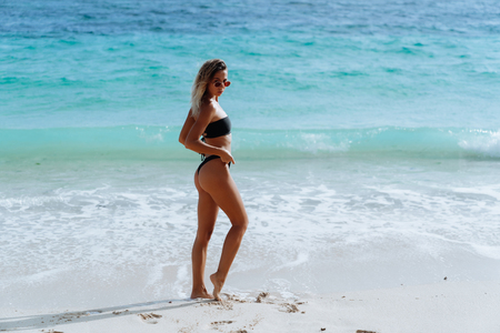 Photo for Side view of slim sexy model posing in swimsuit and sunglasses background of ocean on beach at sunny day - Royalty Free Image