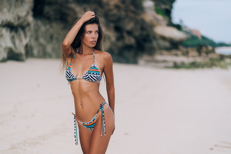 Photo for Beautiful sexy girl in swimwear walking on sandy beach with rock on background - Royalty Free Image