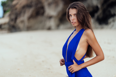 Photo for Beautiful sexy tanned woman in blue swimsuit on white sand beach - Royalty Free Image