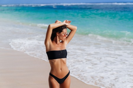 Photo for Beautiful girl in black swimsuit and sunglasses resting near ocean on beach - Royalty Free Image