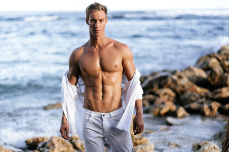 Photo pour Muscular athletic sexy man in white pants with a naked torso on the beach. - image libre de droit