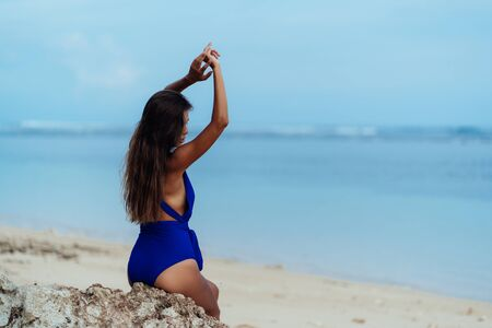 Photo for Back side view sexy girl in blue swimwear relaxing on beach with white sand - Royalty Free Image