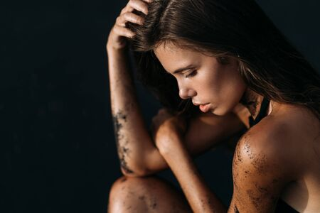 Photo for Portrait of beautiful tanned sensual girl in swimsuit on black sandy beach - Royalty Free Image