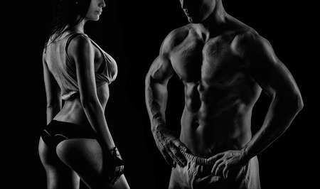 Foto de young muscular guy in the studio, posing for the camera with girl - Imagen libre de derechos