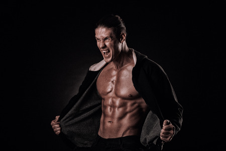 Photo pour young muscular man screams in the studio in hoodie - image libre de droit