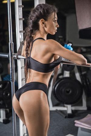 Foto de fitness girl with shaker posing on bench in the gym - Imagen libre de derechos