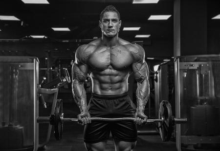 Foto de Male athlete bodybuilder weightlifter, in a modern gym, against a dark background, posing in front of the camera. - Imagen libre de derechos