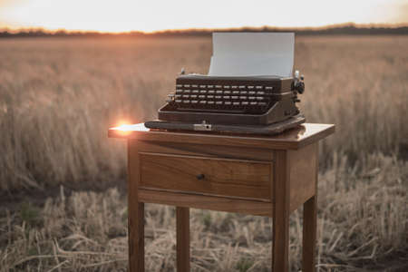 Photo for typewriter on a walnut bedside table in a wheat field at sunset - Royalty Free Image