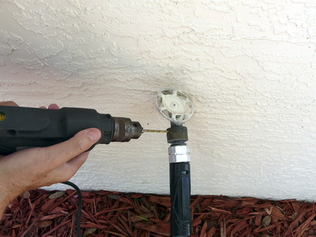 Photo pour A man is using a drill to remove a backflow preventer device to replace a leaking gasket. The device is sometimes required to protect water supplies. - image libre de droit