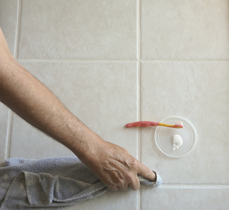 Photo for Male homeowner uses paintbrush and grout color/sealer to paint tile grout lines in the kitchen of his residence to repel oils and prevent stains. - Royalty Free Image