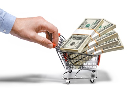 Photo pour businessman s hand   steel grocery cart full of money stacks - isolated on white background - image libre de droit