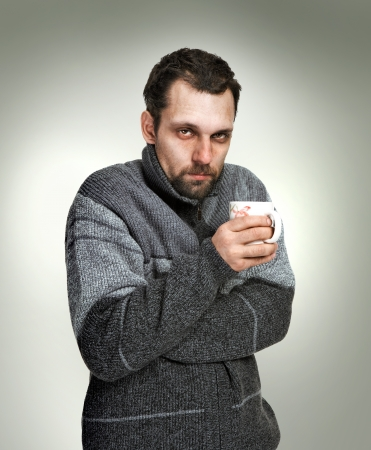 Foto de Cold, sick man dressed in grey sweater holding a cup of tea in hands isolated on grey background looking at the camera - Imagen libre de derechos