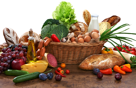 Photo for Large variety of food in wicker basket with goods on old wooden table - Royalty Free Image