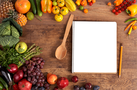 Photo pour open blank ring bound notebook surrounded by a fresh vegetables and pencil on old wooden table - image libre de droit