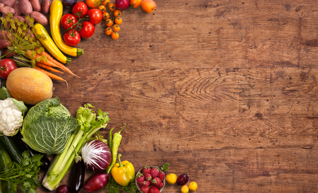 Foto de Healthy food background - studio photo of different fruits and vegetables on old wooden table - Imagen libre de derechos