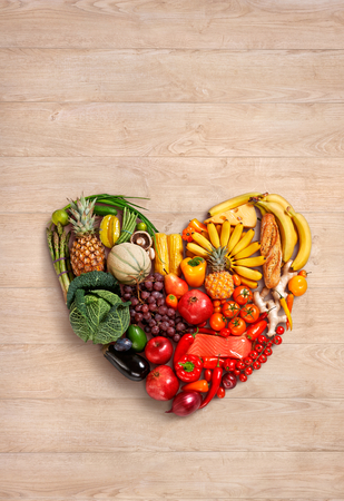Heart symbol - food photography of heart made from different fruits and vegetables on wooden table